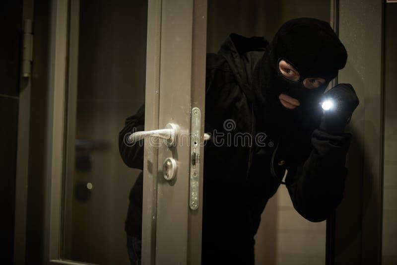 Inbrottstjuvtjuv i maskering Stöt av en lägenhet fotografering för bildbyråer