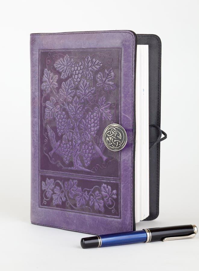inbunden purpur writing för tidskriftsläderpenna arkivbild