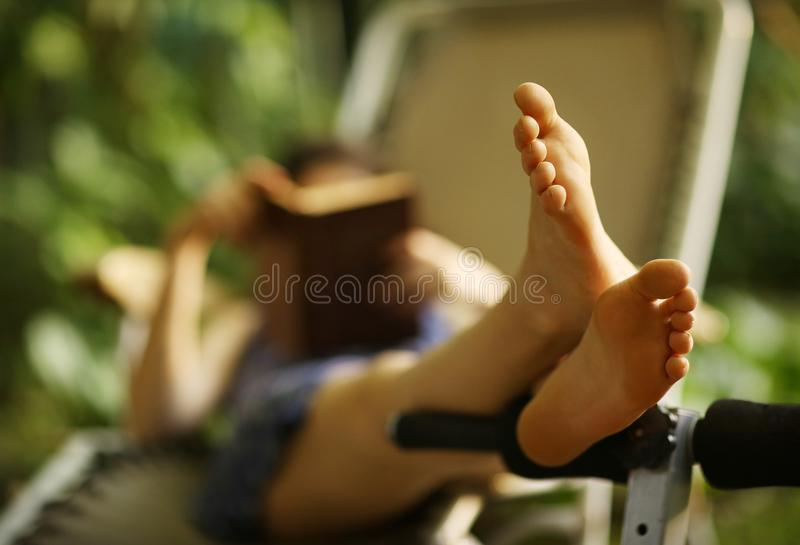 Inbunden tonåringflickaläsebok i hängmatta royaltyfria foton