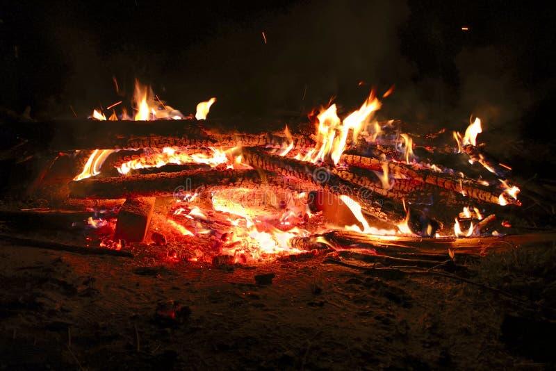 Incêndio da noite Um fogo brilhante da madeira e da escuridão Ramos brilhantemente ardentes das árvores no fogo na noite fotos de stock royalty free