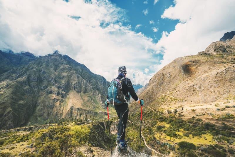 Inca Trail, Peru: 11 de agosto de 2018: Um caminhante masculino está tomando um resto com bengalas e está apreciando a vista boni fotos de stock royalty free