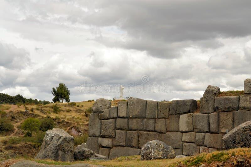 Incafästning Saksaywaman med den Jesus statyn, Cusco fotografering för bildbyråer