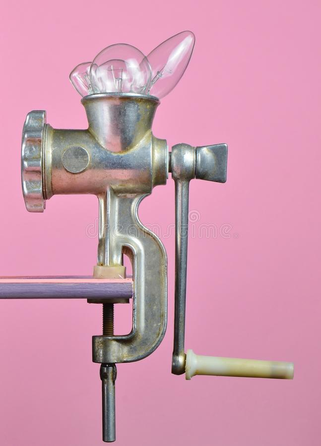 Incandescent bulbs in a retro meat grinder on a pink pastel background, creative and conceptual photo, minimalist trend. Incandescent bulbs in a retro meat stock images
