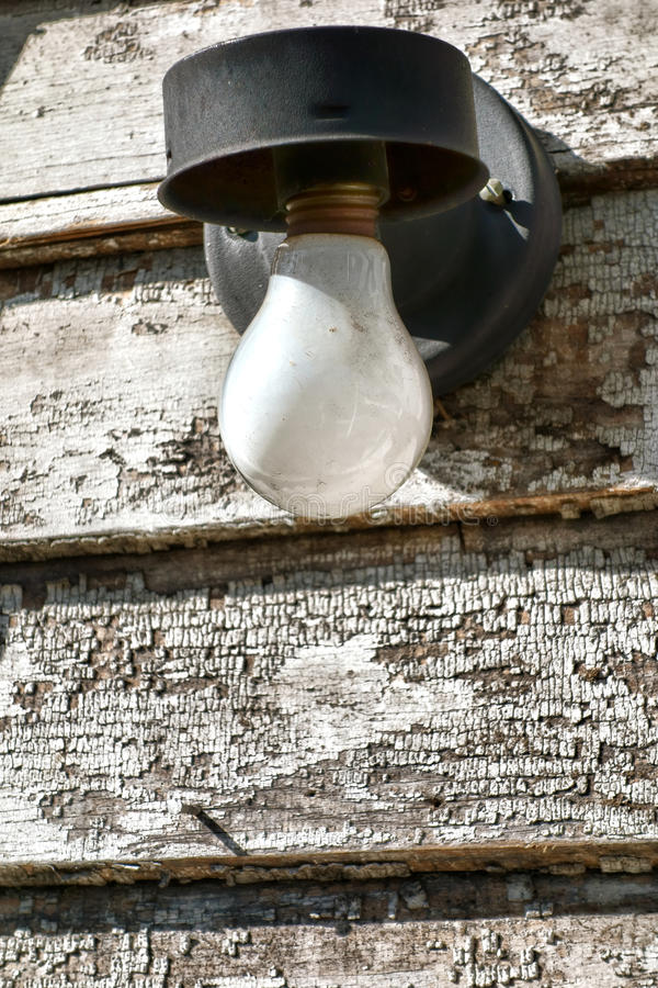 Incandescent Electric Light Bulb on Old Building royalty free stock photography