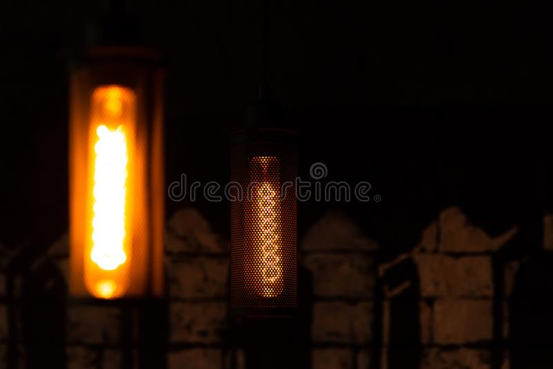 Incandescent lamp. Glowing retro lamp in metal shade. Lamp in the interior stock images