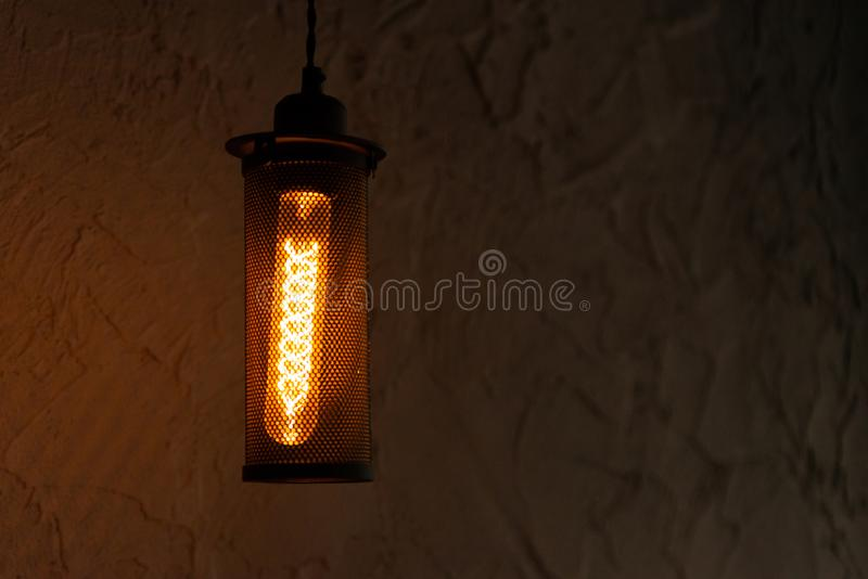 Incandescent lamp. Glowing retro lamp in metal shade. Lamp in the interior stock photography
