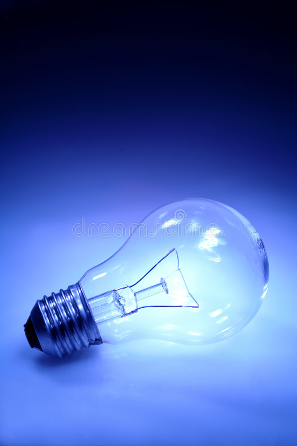 Incandescent light bulb. Details of a clear, incandescent light bulb. Blue tone stock photo