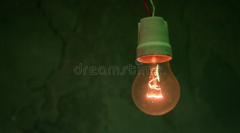 Incandescent light bulb. In front of a green wall royalty free stock photography
