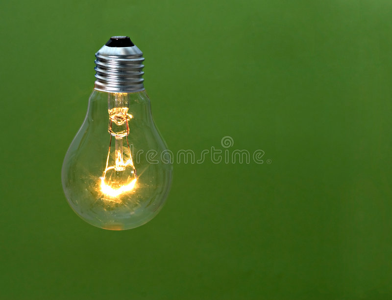Incandescent light bulb. Isolated on green background stock image
