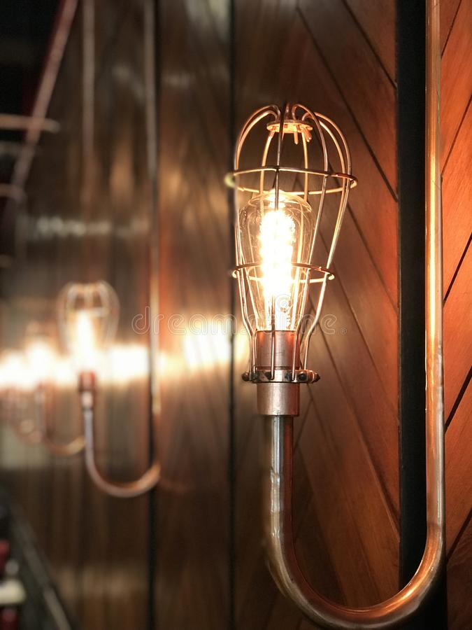 An incandescent light. Warm glow of a Tungsten lamp reflects on wood. An incandescent light bulb, incandescent lamp or incandescent light globe is an electric royalty free stock photos