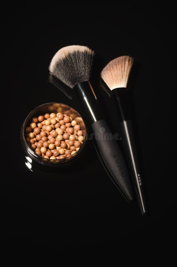 Incandescenza di Avon che bronza le perle isolate su fondo scuro immagine stock