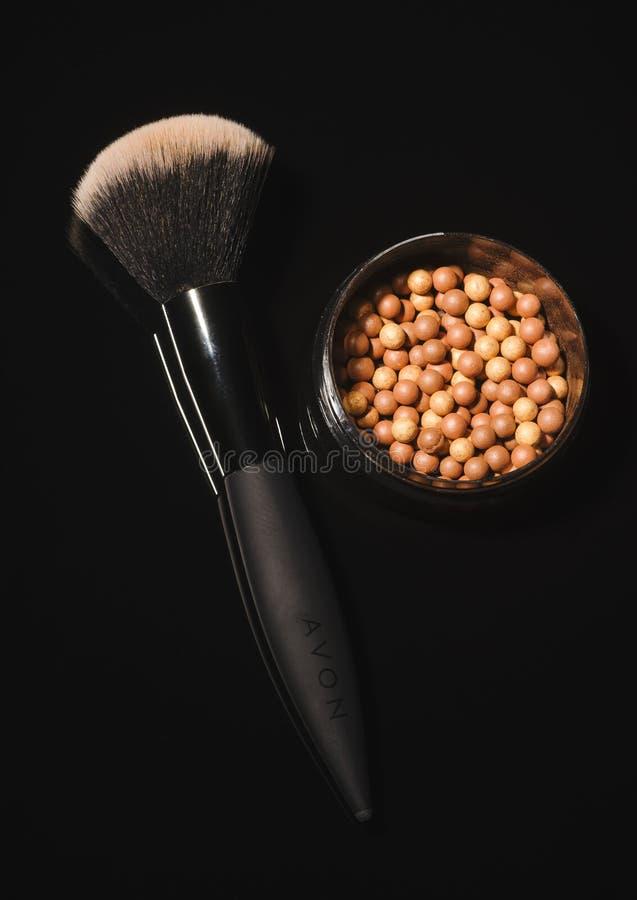 Incandescenza di Avon che bronza le perle isolate su fondo scuro immagini stock