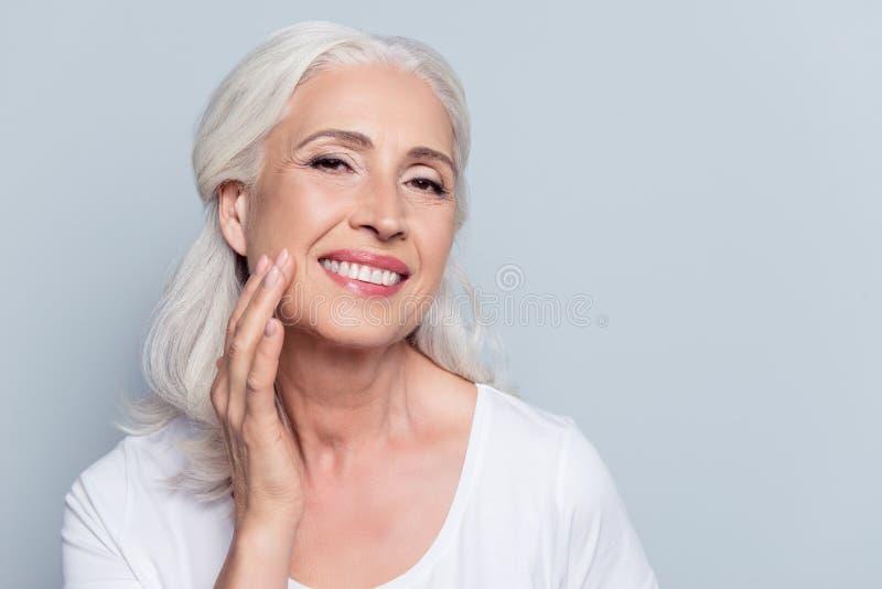 Incantando, donna graziosa e anziana che tocca la sua pelle molle perfetta del fronte immagini stock libere da diritti