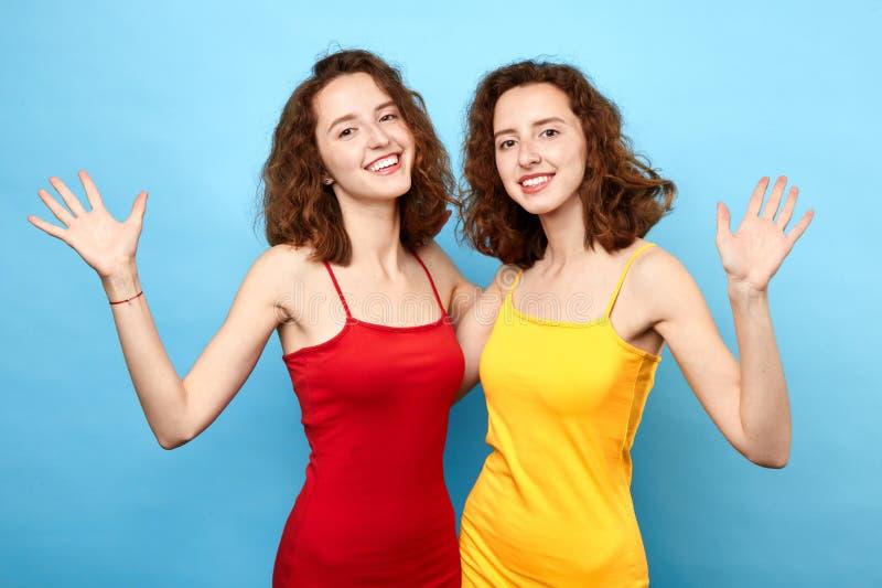 Incantare le donne felici con le palme alzate dice ciao fotografie stock libere da diritti