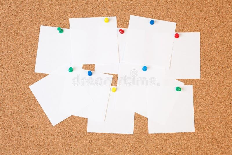 Incarti le note sulla scheda del sughero fotografia stock