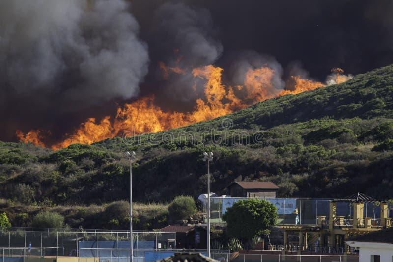 Incendio violento vicino alle case fotografie stock