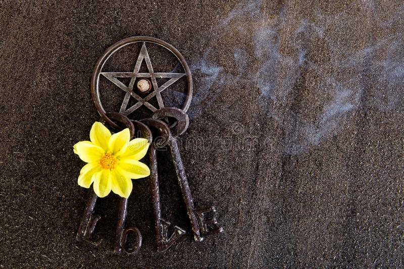 Incense burning in gray metal pentagram with love keyring on slate background with yellow dahlia flower royalty free stock photo