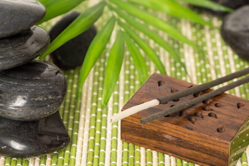Incense i bastoni con le pietre nere del basalto e la foglia verde, sulla stuoia di bambù immagini stock
