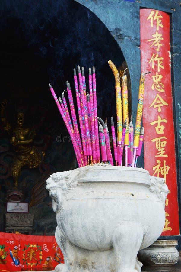 Incense los palillos en la hornilla de incienso en el templo imagenes de archivo