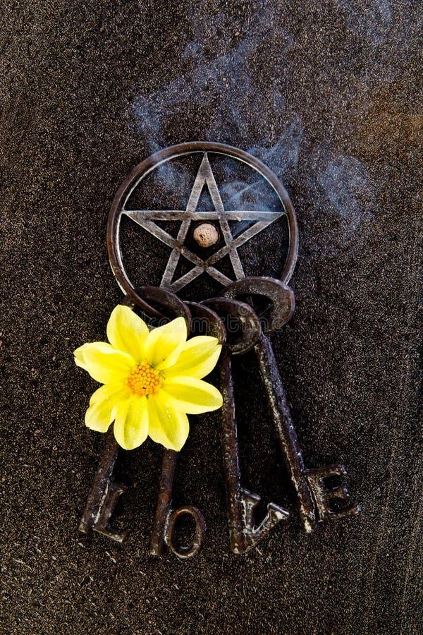 Incense o burning no pentagram cinzento do metal com o keyring do amor em precários fotos de stock