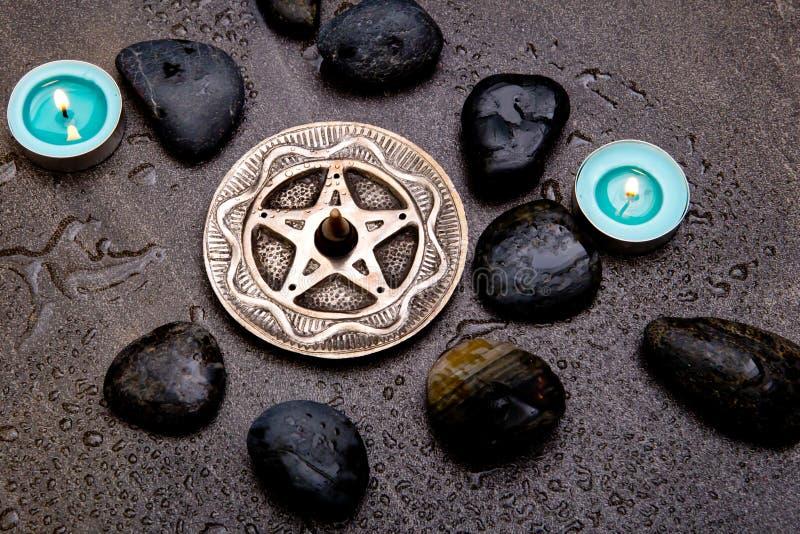 Incense o burning no pentagram de prata com velas e preto azuis fotos de stock royalty free