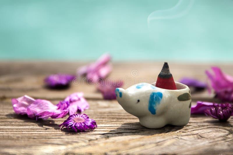 Incense o cone ou a goma benjamin no queimador de incenso cerâmico com seco fotografia de stock