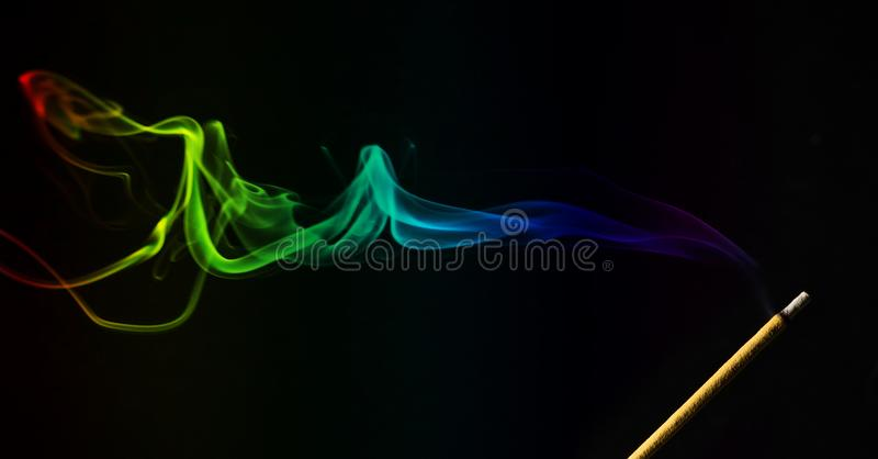 Incense smoke with stick. Colored smoke with incense stick over black stock photography