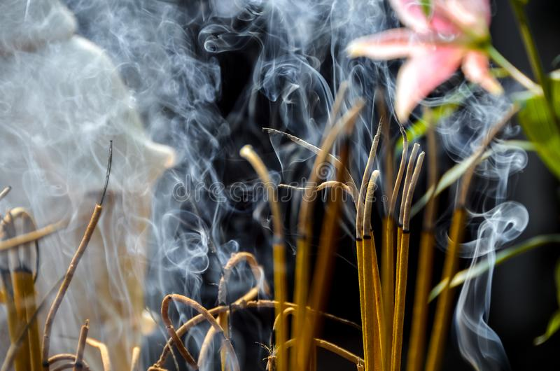 Incense sticks in temple in Vietnam. Incense sticks burning and smoking in temple in Vietnam on black background royalty free stock images