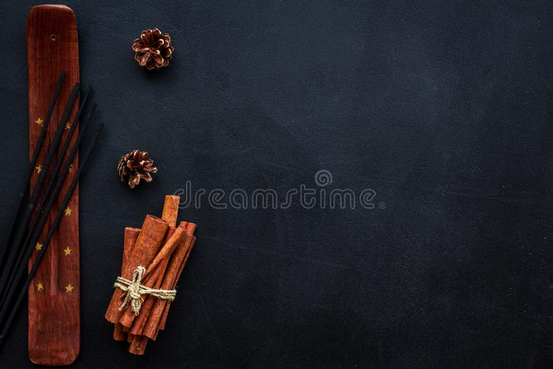 Incense sticks with cone and cinnamon for fresh air on dark background top view mock up stock image