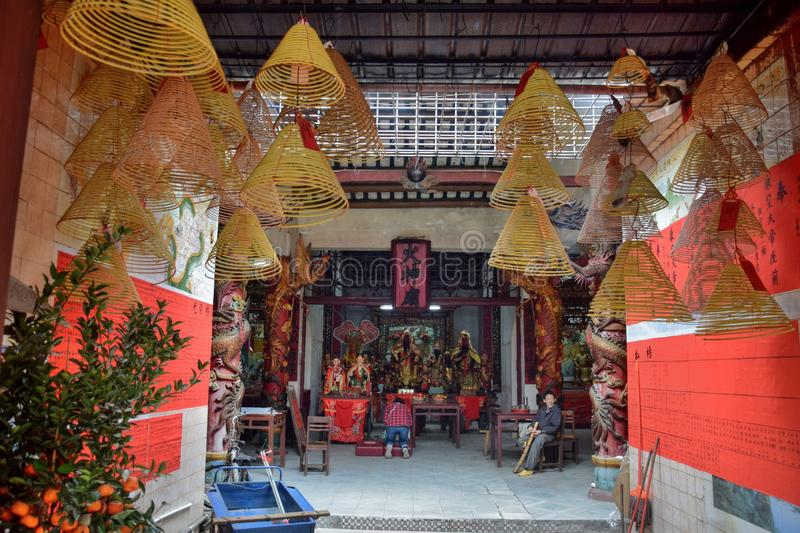 Taoist temple dedicated to Fire God in Gaozhou in China. Incense sticks hung inside the taoist temple. Fire God shrine inside the taoist temple. Translation royalty free stock photo