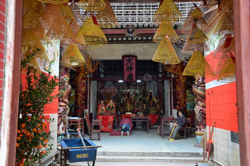 Taoist temple dedicated to Fire God in Gaozhou in China. Incense sticks hung inside the taoist temple. Fire God shrine inside the taoist temple. Translation stock images