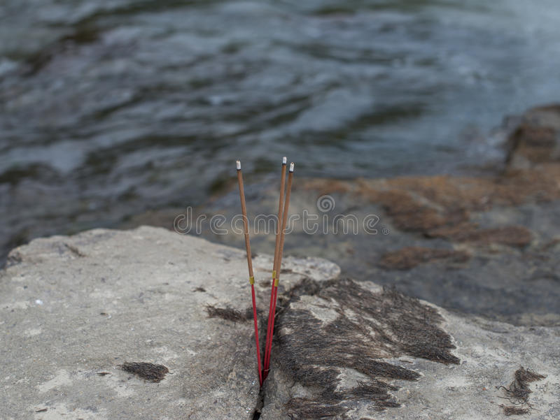Incense sticks in stone on the banks of the river. Selective focus royalty free stock photo