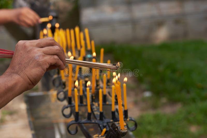 Incenso ardente das mãos dos povos das velas imagem de stock