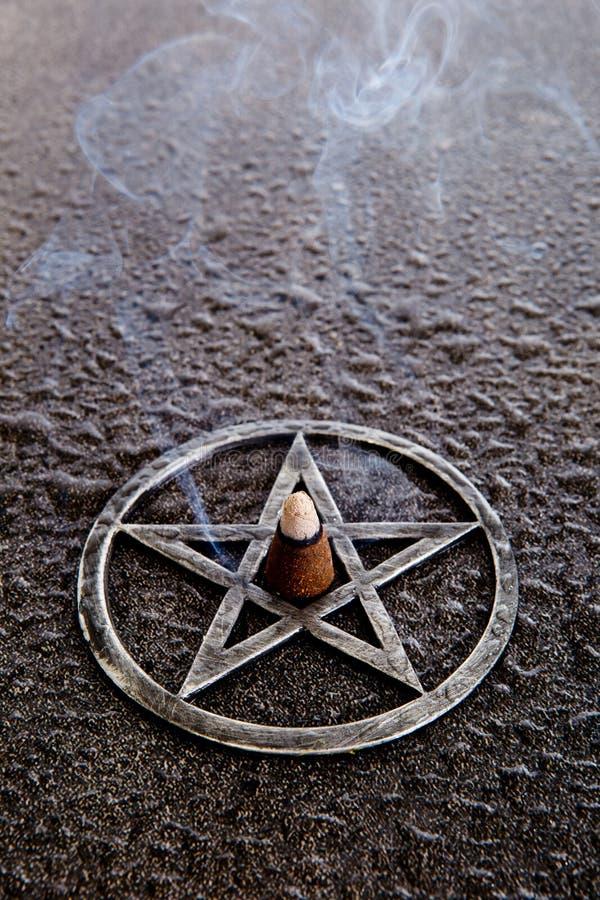 Incenso ardente no centro do pentagram cinzento do metal no backg da ardósia fotografia de stock