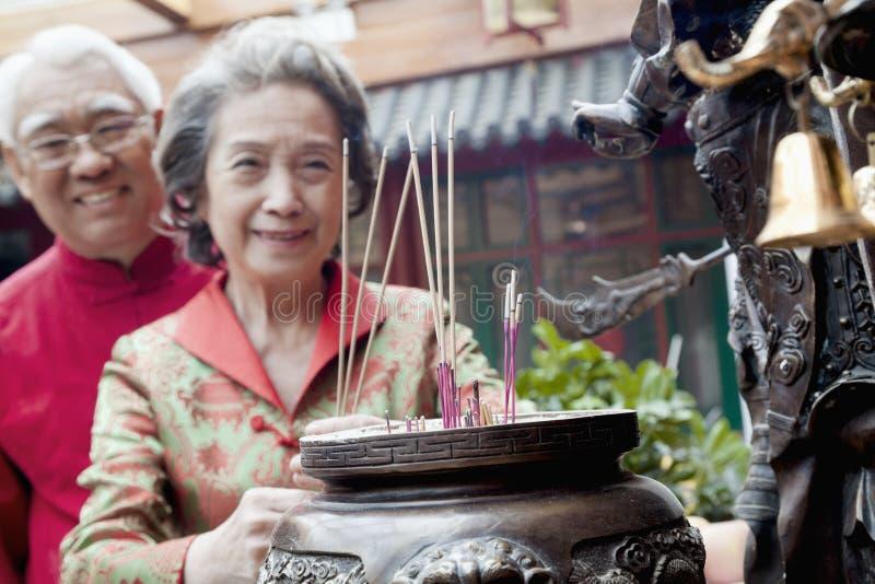 Incenso d'offerta al tempio, Pechino delle coppie senior fotografia stock