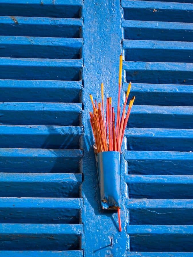 Incenso rosso sugli otturatori blu della finestra fotografia stock