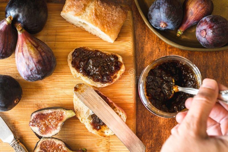 Inceppamento del fico in un barattolo, fetta di pane e fichi freschi su un tavolo da cucina di legno Vicino su, vista superiore,  fotografia stock