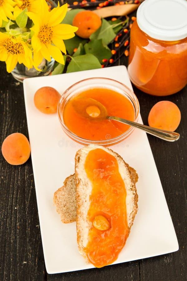 Inceppamento delizioso dell'albicocca su una fetta di pane con burro fotografia stock libera da diritti