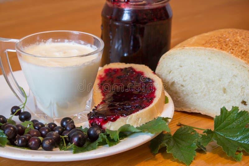Inceppamento su pane e su latte, preparazione di un inceppamento fatto dell'uva passa con pane e un bicchiere di latte immagini stock