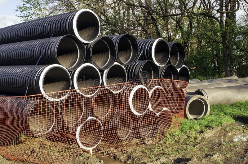 18 inch corrugated plastic pipes stacked up for a construction project. On a sunny day stock images
