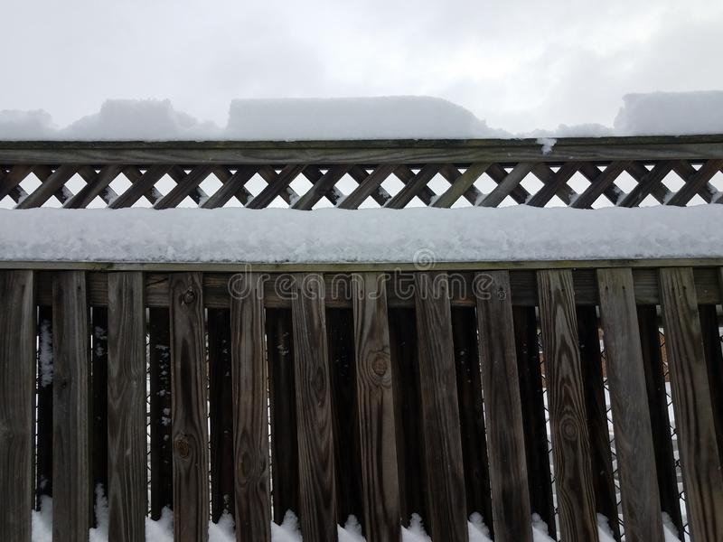 Inches of white snow on wood fence. Inches of white snow and ice on wooden fence in winter stock photos