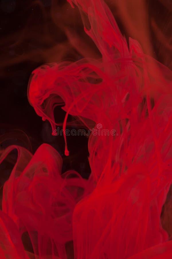 Inchiostro rosso verticale in acqua su fondo nero che somiglia al demone fotografie stock libere da diritti