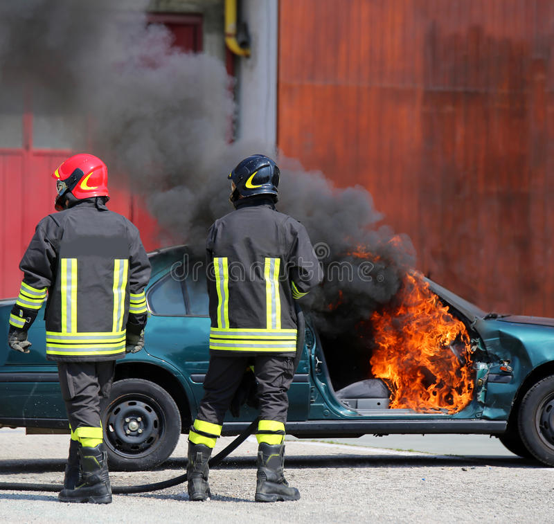 Incident car with flames and black smoke and two firefighters. Incident broken car with flames and black smoke and two firefighters who turn off the fire stock image