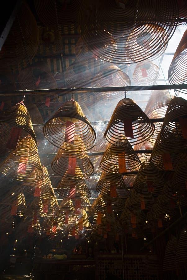 Incienso y rayos crepusculares en templo del MES del hombre foto de archivo