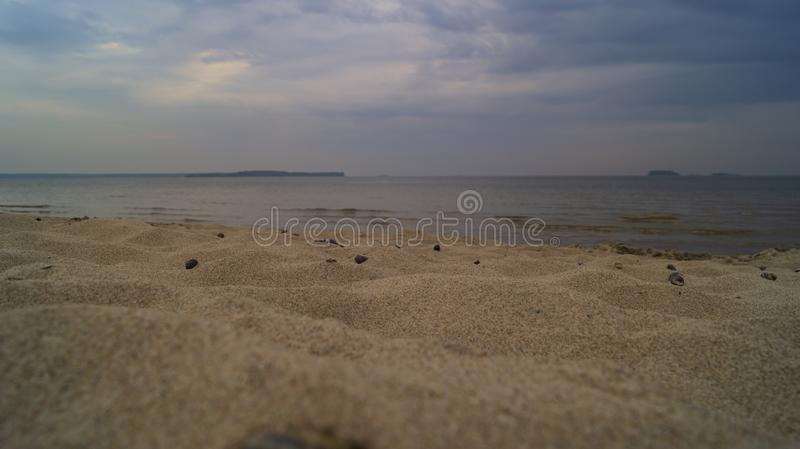 Inclement weather on the sandy beach. Clouds in the sky, on the sand are snails royalty free stock images