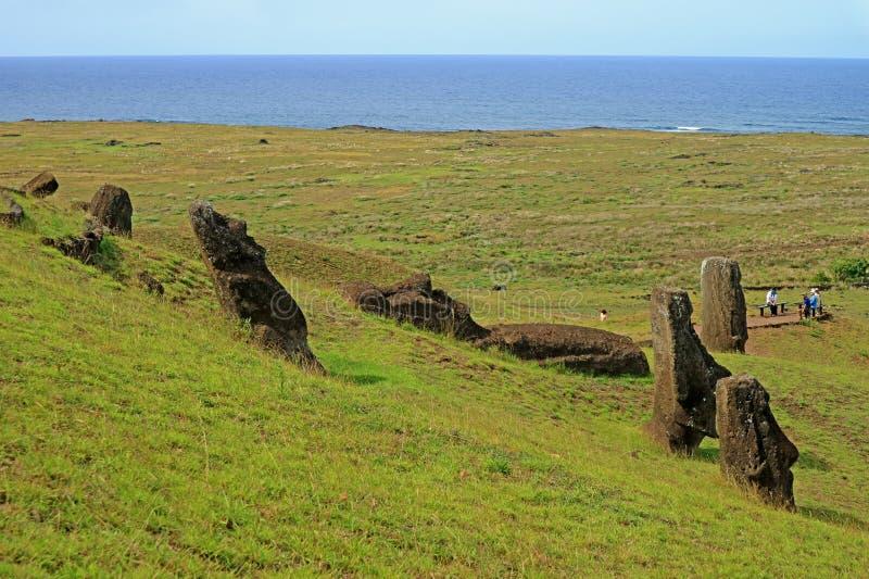 A inclinação completamente de estátuas abandonadas de Moai do gigante do vulcão de Rano Raraku com o Oceano Pacífico no contexto, imagens de stock royalty free