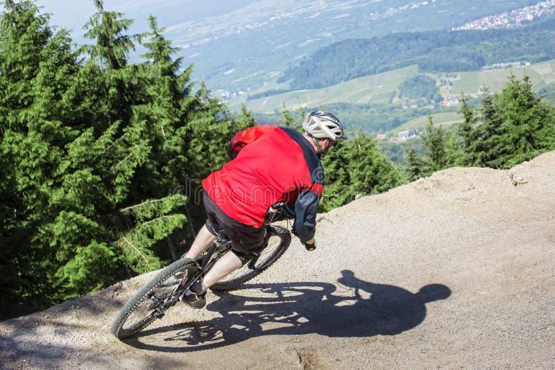 Inclinação da gravidade do cavaleiro do Mountain bike fotografia de stock