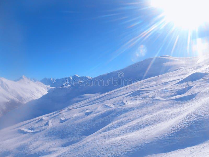 Inclinação da neve do esqui e céu azul com sol imagem de stock