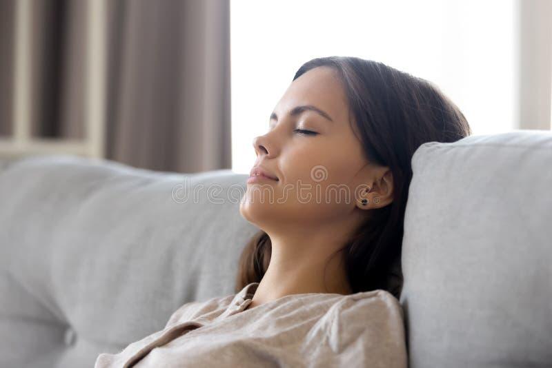 Inclinação de relaxamento da mulher calma sereno no sofá confortável que tem a sesta foto de stock royalty free