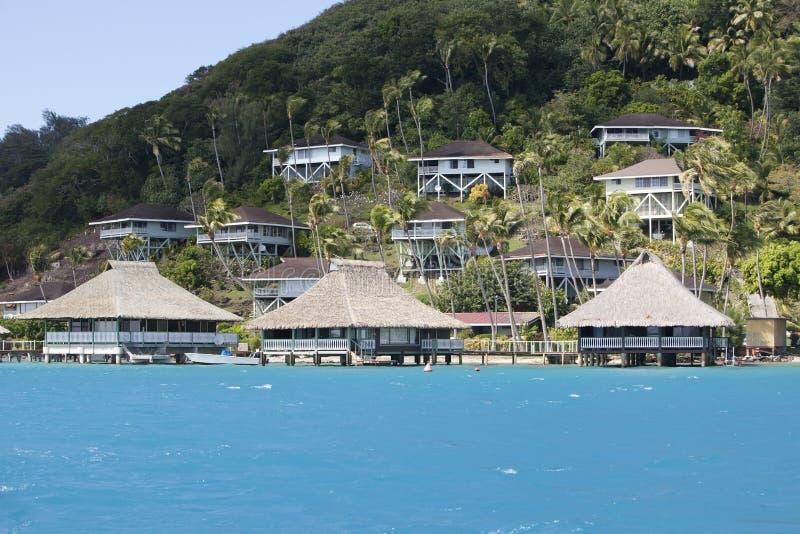 Inclinação do monte pelo mar e pelos alojamentos em uma inclinação polynesia foto de stock